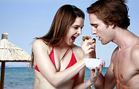 Young adult couple feeding each other