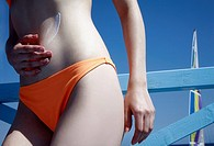Female young adult applying suntan lotion