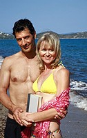 Mature adult couple on beach with book