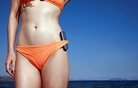 Female young adult in bikini with cell phone