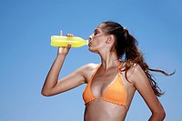 Female young adult drinking juice in bikini