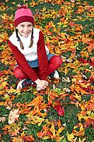 Girl sitting amongst leaves