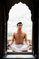 young man meditating in doorway