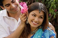 young man putting flowers behind young woman's ear