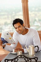 man reading morning newspaper, having hot drink