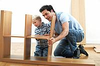 Father and son assembling bookshelf