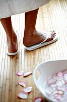 Woman standing in flip flops next to footbath