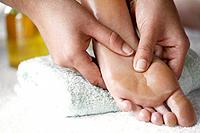 Massage therapist applying pressure to foot with her thumbs