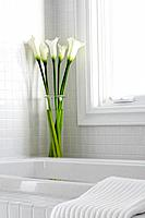 Vase of white calla lilies on edge of tub