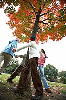 Children holding hands and dancing around tree