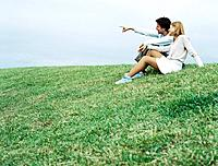 Couple sitting on grass, looking toward distance
