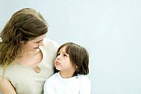 Mother and young son looking at each other, boy frowning