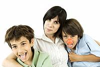 Mother and two sons, boys sticking out their tongues, one wearing clown´s nose