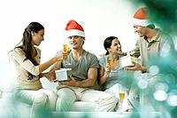 Two couples exchanging Christmas gifts, drinking champagne, men wearing Santa hats