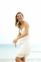 Woman in sundress at the beach, smiling, laughing