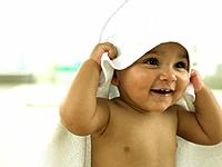 Baby with towel over head smiling