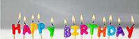 Coloured letter Candles lit up and spelling out Happy Birthday