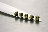 Five green peppercorns on a knife blade