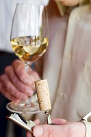 Man holding wine cork on corkscrew and glass of white wine