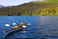 Father & sons sea kayaking in tandem kayak on Bear Lake Kenai Peninsula Alaska Summer