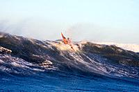 Man sea kayaking right at the crest of huge breaking wave off Homer Kachemak Bay Alaska Winter