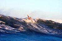 Man sea kayaking right at the crest of huge breaking wave off Homer Kachemak Bay Alaska Winter
