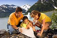 Family inspects chunk of ice from Portage Lake while out hiking Chugach National Forest SC Alaska