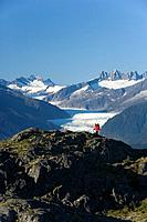 Man hiking in Alaska´s Tongass National Forest with view of Mendenhall Glacier near Juneau Alaska southeast Autumn