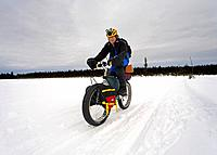 Man on trail in extreme crosscountry bike race Susitna 100 Southcentral Alaska Winter