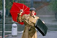 Businessman w/ umbrella in rainstorm Anchorage SC AK summer portrait