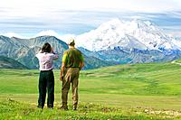 Man and woman tourist standing on tundra viewing Mt McKinley from Thorofare Pass area Denali National Park Interior Alaska summer