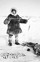 Historical image of person dressed in a native parka and mukluks ice fishing winter Alaska