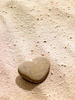 Heart shaped stone in sand