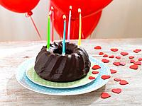 Chocolate pound cake with lit candles and hearts