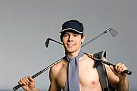 Young man carrying golf clubs, studio shot