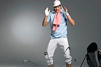 Young man looking at golf clubs, studio shot (thumbnail)