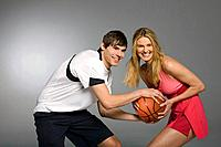 Young couple playing basketball, studio shot