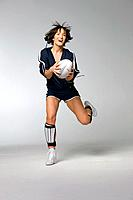 Young woman catching football, studio shot