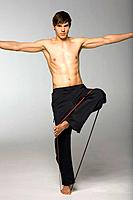 Young man balancing on one leg, studio shot