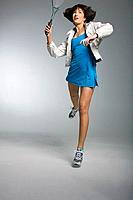 Young woman playing tennis, studio shot