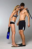 Young couple looking at snorkel gear, studio shot