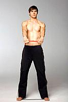 Young man stretching on elastic band, studio shot