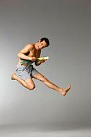 Mid adult man with leek jumping in air (thumbnail)