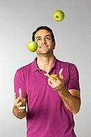 Mid adult man juggling green apples