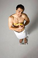 Young adult man on weight scale (thumbnail)