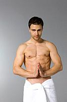 Young man in towel meditating