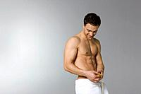 Young man wearing towel measuring waist