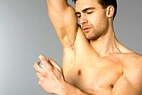 Young man spraying deodorant to his underarm