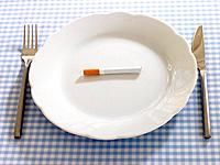 Close_up of a cigarette in a plate with a fork and a table knife