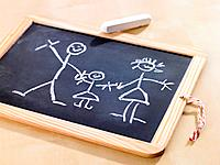 Close_up of a child's drawing on a chalkboard depicting a family